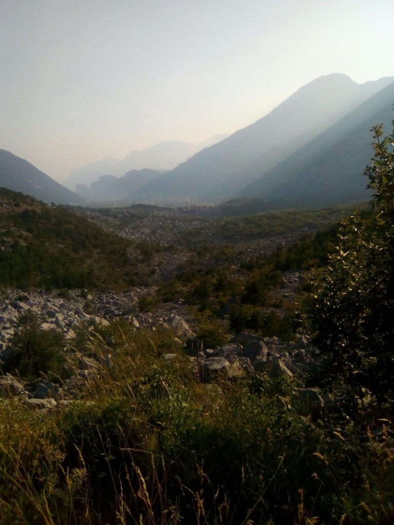 Le Marocche di Dro, una frana provocata dal ritiro dei ghiacciai. Il Lago di Garda è poco dopo i rilievi più bassi sullo sfondo.